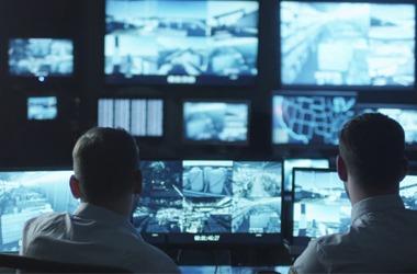 Two men checking surveillance videos for criminal activity